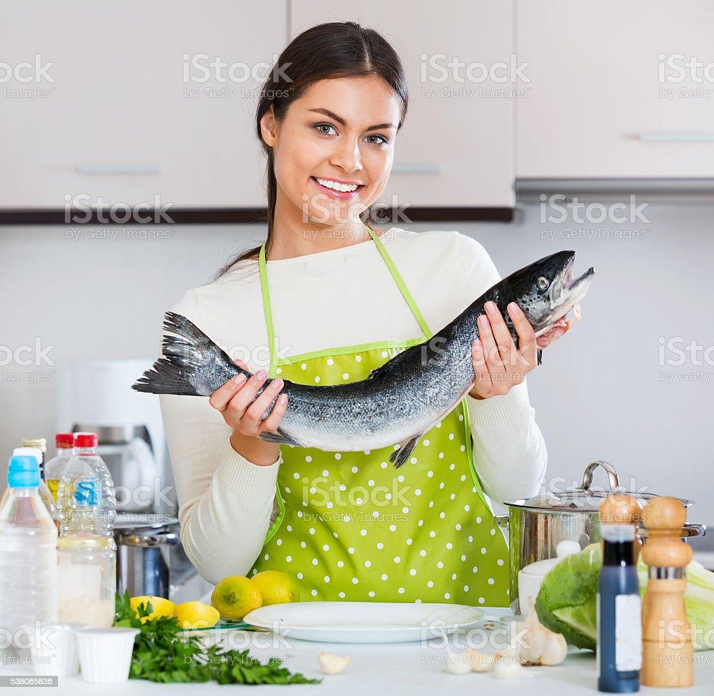 Attractive brunette girl preparing trout dish stock photo