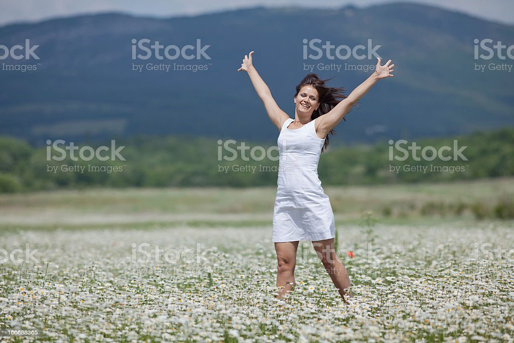 Attractive brunette in chamomile meadow royalty-free stock photo