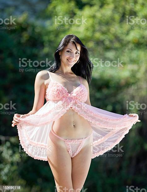 Young woman in transparent lingerie is posing in the park