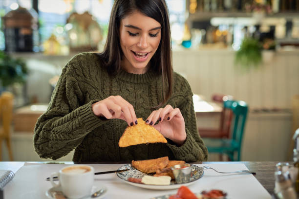 Attractive brunette sitting in restaurant in morning and eating french toast for breakfast. stock photo