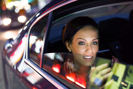 Attractive brunette texting on the phone in a car
