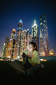 Attractive brunette texting on the phone in front skyscrapers in Dubai