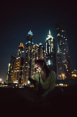 Attractive brunette texting on the phone in front skyscrapers in Dubai.