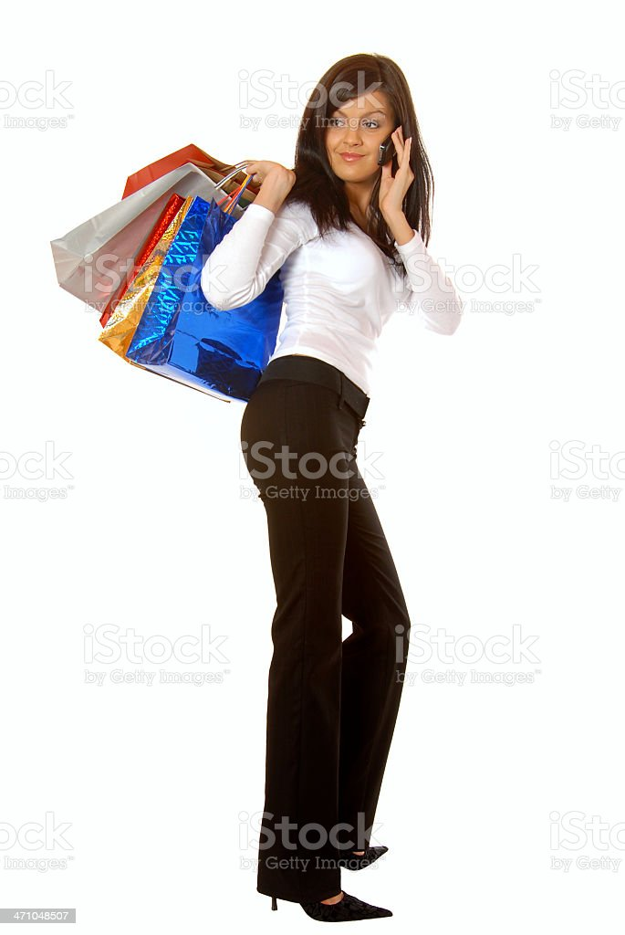 Attractive brunette with mobile phone and shopping bags royalty-free stock photo