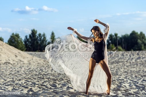 Attractive brunette woman in black body and translucent beach cover up posing on sandy beach at sunset. fluttering dress with hands and looking away. Fashion outdoor shot in the summertime.