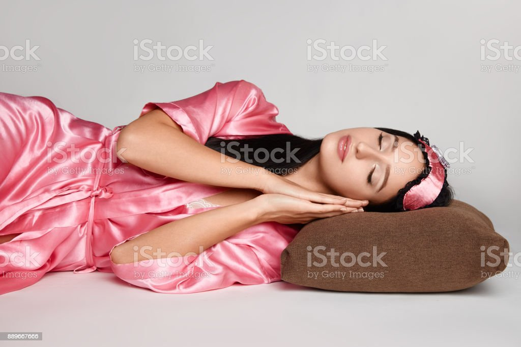 Attractive brunette woman in pink gown is laying on pillow with eyes...