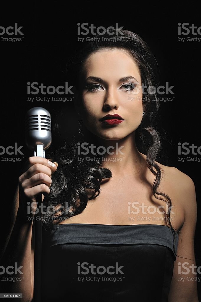 Attractive brunette woman with a retro microphone royalty-free stock photo