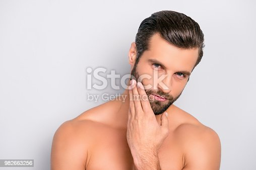 istock Attractive, brutal, modern, manly, virile, confident, dreamy, naked man touching his perfect, ideal face skin, holding hand on beard, cheek, looking at camera, isolated over gray background 982663256