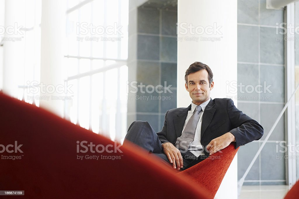 Attractive business man sitting and smiling confidently stock photo