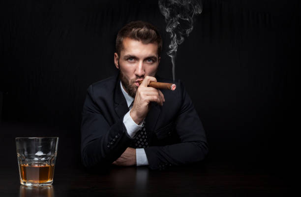 Attractive business man with a cigar and a drink stock photo