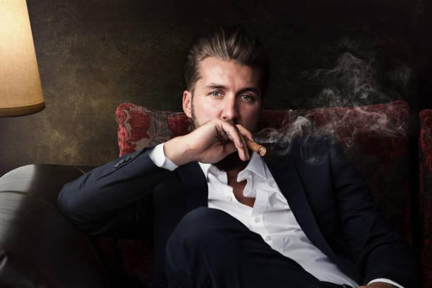 aantrekkelijke zakenman met een sigaar is ontspannen op de bank - guy with cigar stockfoto's en -beelden