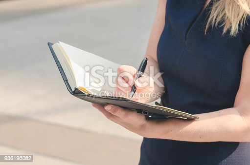 attractive business woman hand writing on notebook paper with pencil at outdoor in the city with sun light.