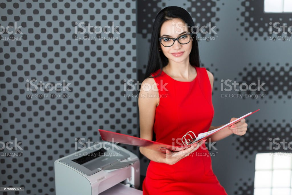 Attractive businesslady in red dress and glasses stand near the printer and hold paper folder royalty-free stock photo