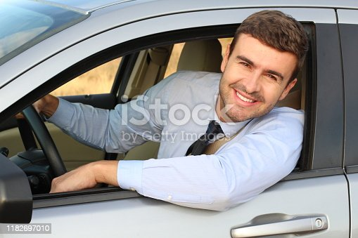1138561232 istock photo Attractive businessman driving a car 1182697010