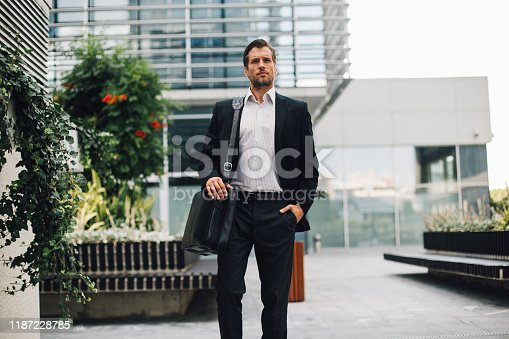 Businessman wearing black suit and bag on shoulder