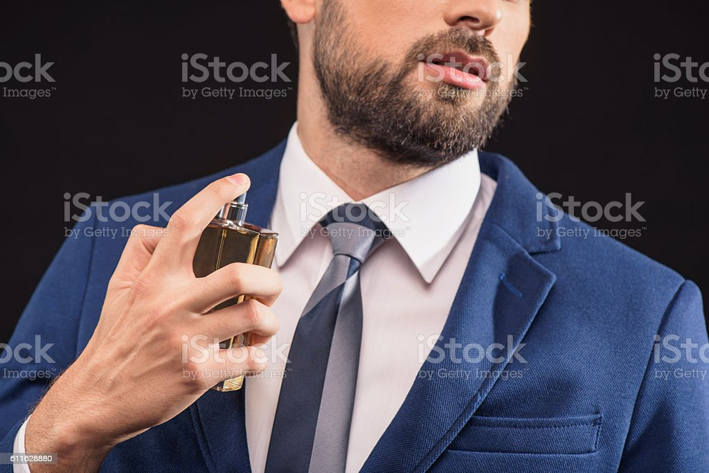 Attractive businessman wearing scent with pleasure stock photo