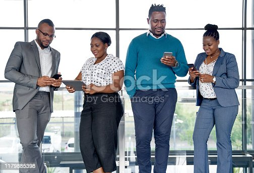 istock Attractive businessmen and businesswomen holding cellphones and tablets for management of successful startup 1179885398