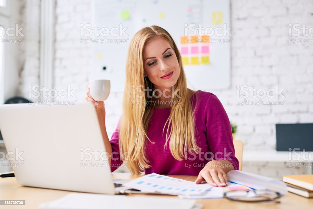 Attractive businesswoman drinking coffee while doing paperwork in her modern office stock photo
