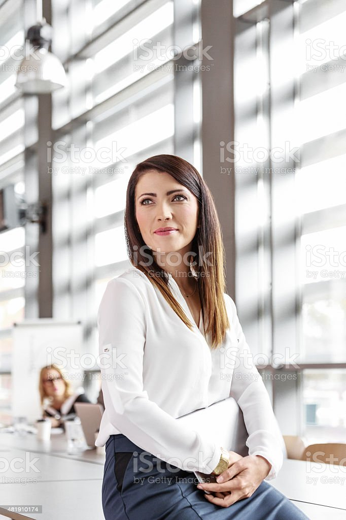 Attractive businesswoman in an office, holding a digital tablet Friendly businesswoman wearing white shirt sitting in a board room in an office, holding a digital tablet in hands, looking away. 2015 Stock Photo