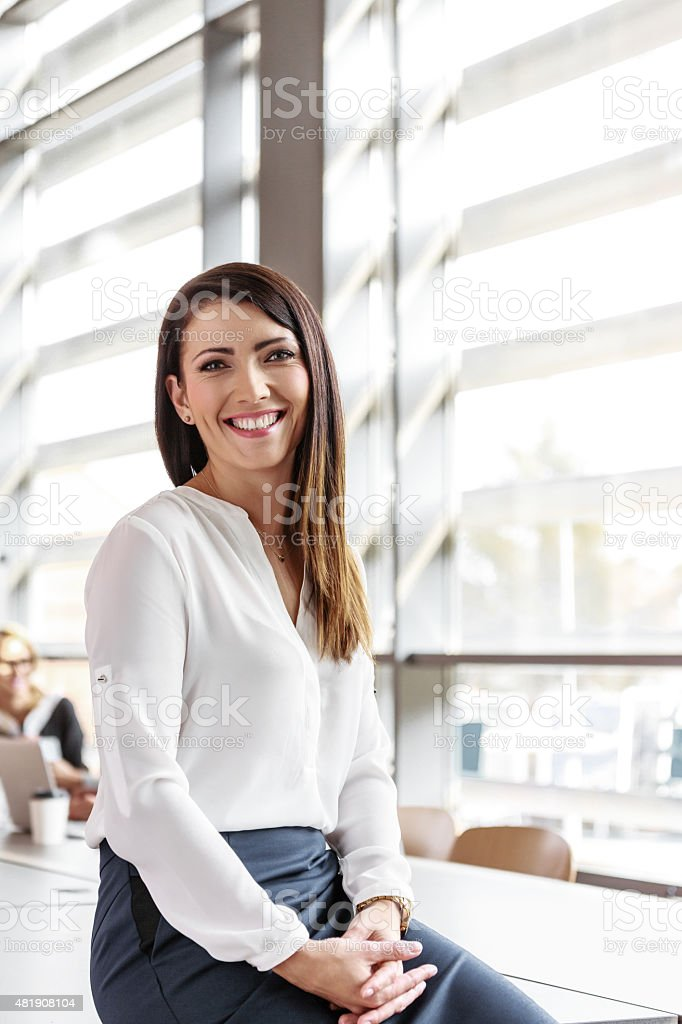Attractive businesswoman in an office Friendly businesswoman wearing white shirt sitting in a board room in an office, smiling at the camera. 2015 Stock Photo