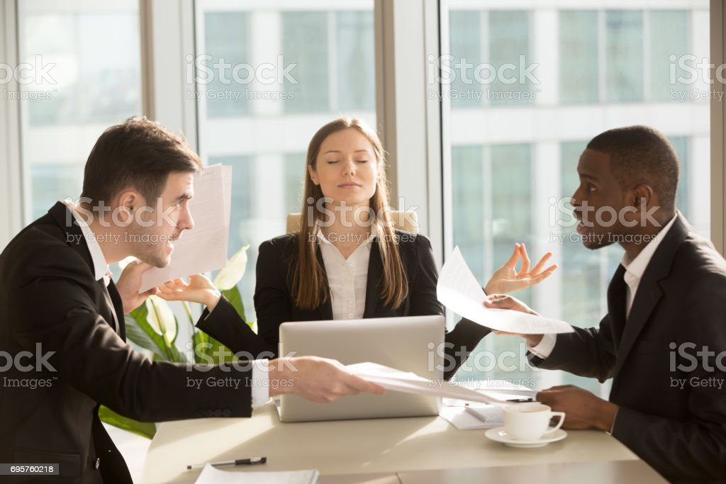 Attractive businesswoman meditating with eyes closed near arguing office workers stock photo