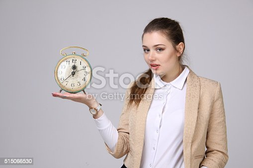 Young attractive woman showing clock, on gray background