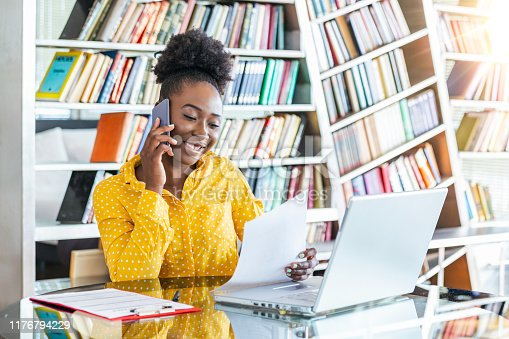 1053499704 istock photo Attractive businesswoman, speaking on the phone, African American woman at training seminar, female business leader going true paperwork at her office 1176794229