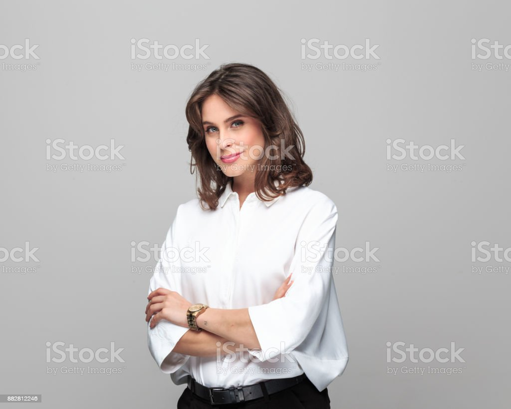 Attractive businesswoman standing with her arms crossed Portrait of attractive businesswoman standing with her arms crossed against grey background. 25-29 Years Stock Photo