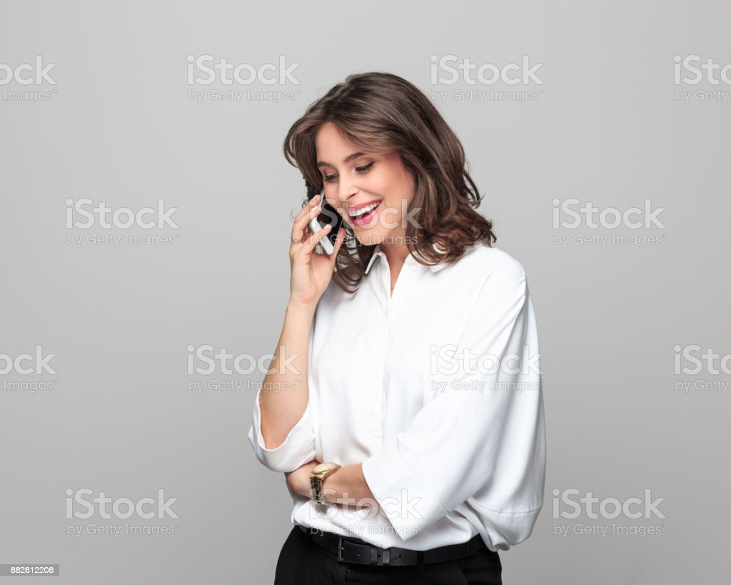 Attractive businesswoman talking on mobile phone Portrait of attractive businesswoman talking on mobile phone while standing against grey background. 25-29 Years Stock Photo