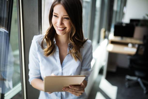 Attraktive Geschäftsfrau mit einem digitalen Tablet, während sie vor den Fenstern steht – Foto