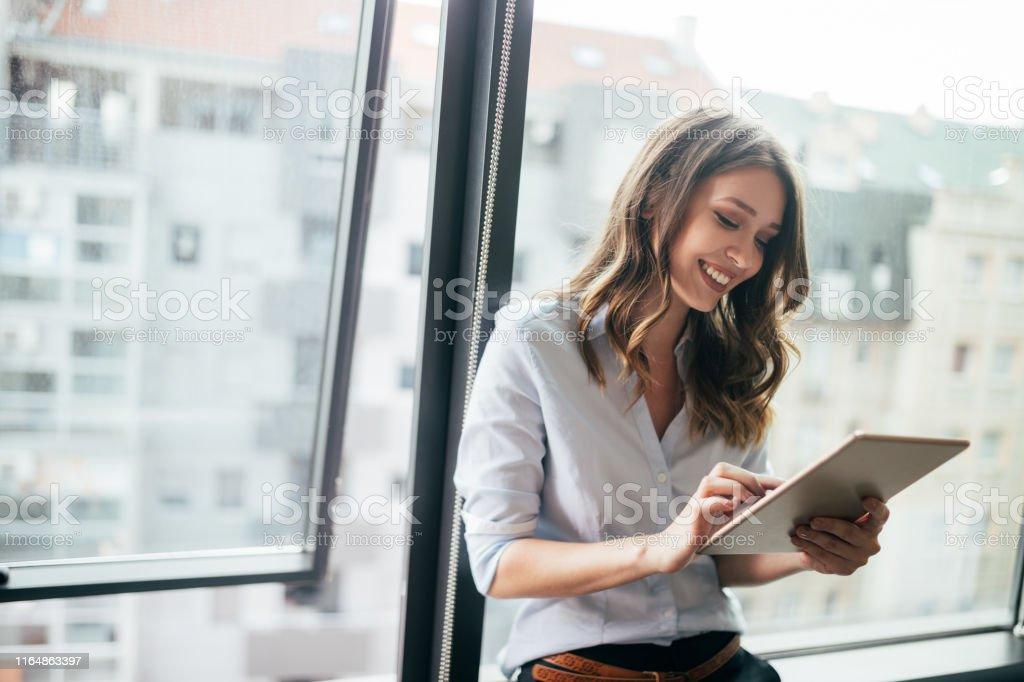 Femme d'affaires attirante utilisant une tablette numérique tout en restant devant des fenêtres - Photo de Adulte libre de droits