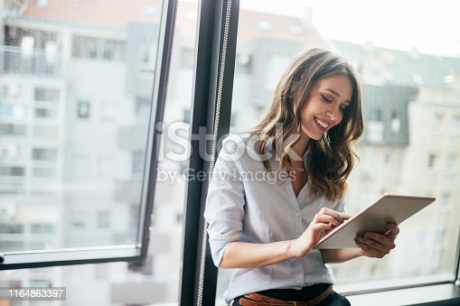 Young businesswoman using a digital tablet while standing in front of windows in office