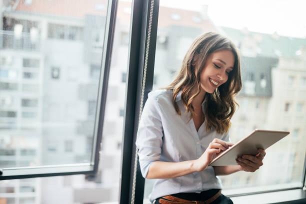 站在窗前使用數位平板電腦的迷人女商人 - 幸福 個照片及圖片檔