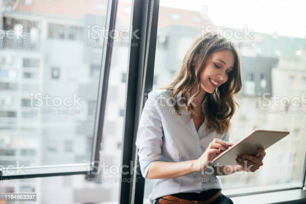 Photo libre de droit de Femme Daffaires Attirante Utilisant Une Tablette Numérique Tout En Restant Devant Des Fenêtres banque d'images et plus d'images libres de droit de Adulte
