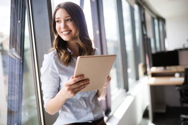 Attractive businesswoman using a digital tablet while standing in front of windows stock photo