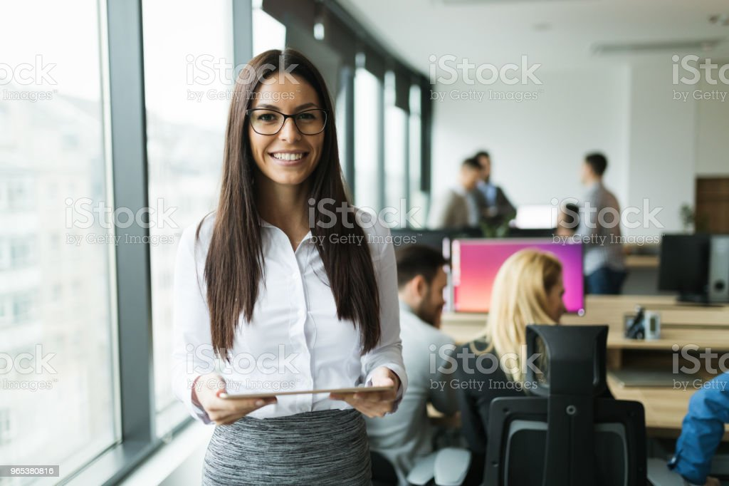 Attractive businesswoman using digital tablet in office stock photo