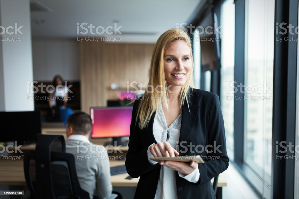Attractive businesswoman using digital tablet in office zbiór zdjęć royalty-free