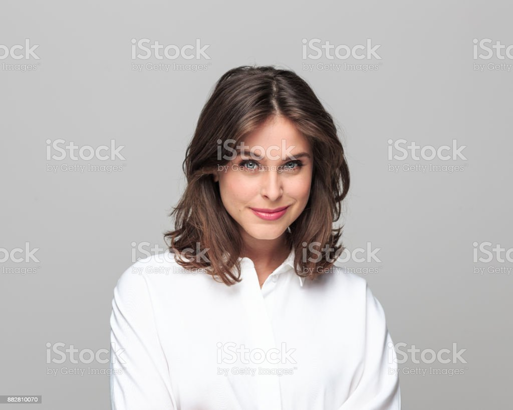 Attractive businesswoman with a beautiful smile Close up portrait of attractive businesswoman standing against grey background and looking at camera with a beautiful smile on her face. 25-29 Years Stock Photo