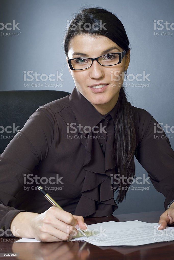 attractive businesswoman with glasses signing documents royalty-free stock photo