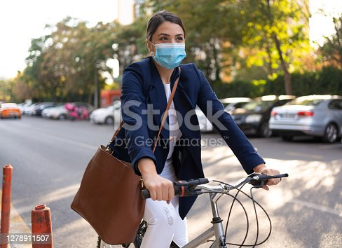 Attractive businesswoman with protective face mask is commuting by bicycle during corona virüs\nepidemic