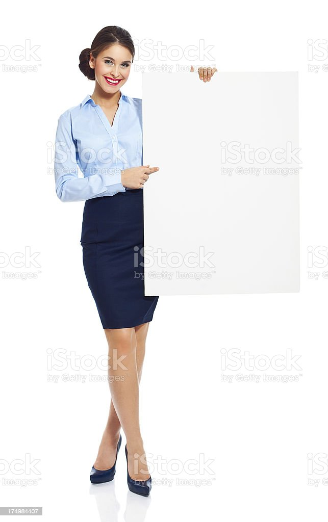 Attractive businesswoman with whiteboard Full lenght portrait of attractive businesswoman standing against white background and holding a whiteboard in hands, smiling at the camera. 20-24 Years Stock Photo