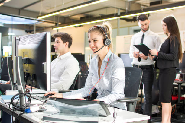 Attractive businesswoman working in call center, surrounded by colleagues.  Online support. stock photo