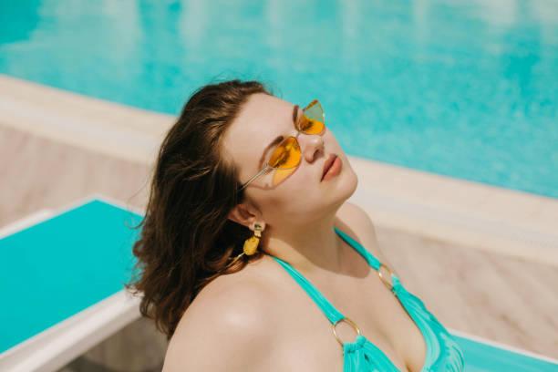 黄色のサングラスで魅力的な巨乳曲線美の女性とプールで休んで青い水着。 - real bodies ストックフォトと画像