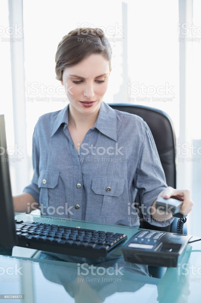 Attractive calm businesswoman hanging up the telephone stock photo