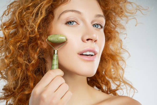 Attractive calm red-haired female massaging her cheek stock photo