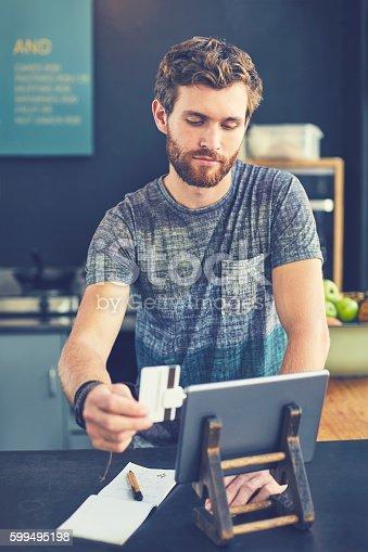 178974134 istock photo Attractive cashier swiping card digital tablet 599495198