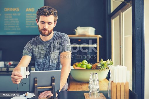 178974134 istock photo Attractive cashier swiping credit card on reader 599498574