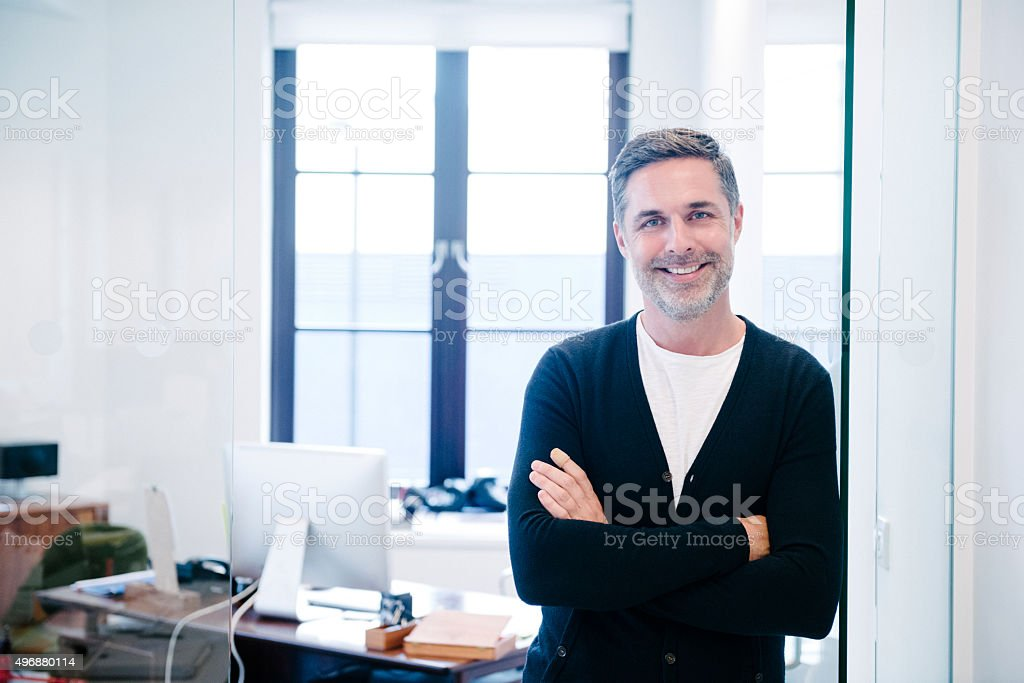 Attractive casual businessman in modern office, arms folded stock photo
