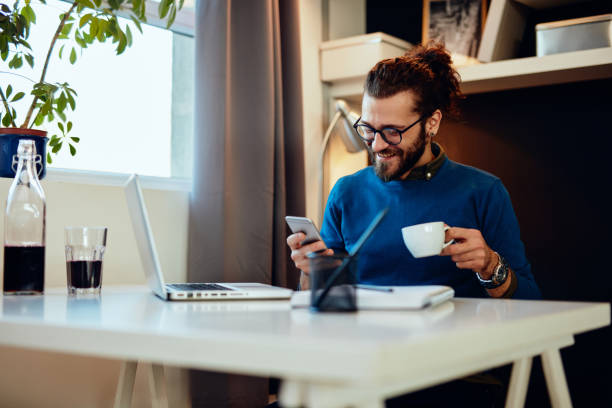 Attractive caucasian bearded entrepreneur sitting in his office, using smart phone and taking a break from work. stock photo