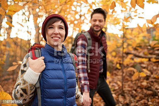 Portait of an attractive millennial couple walking in autumn nature with backpacks and trekking on a path surrounded by orange leaves